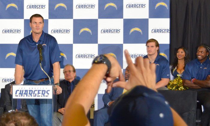 """Chargers quarterback Philip Rivers speaks at a rally celebrating the NFL team's move to Los Angeles from San Diego, while a fan forms the letters """"LA"""" with his hands, in Inglewood, Calif. on Jan. 18. (Sarah Le/Epoch Times)"""