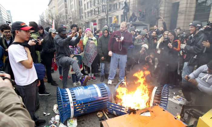 Protesters burn trash cans during the demonstration downtown Washington on Jan. 20, 2017, during the inauguration of President Donald Trump. ( AP Photo/Jose Luis Magana)