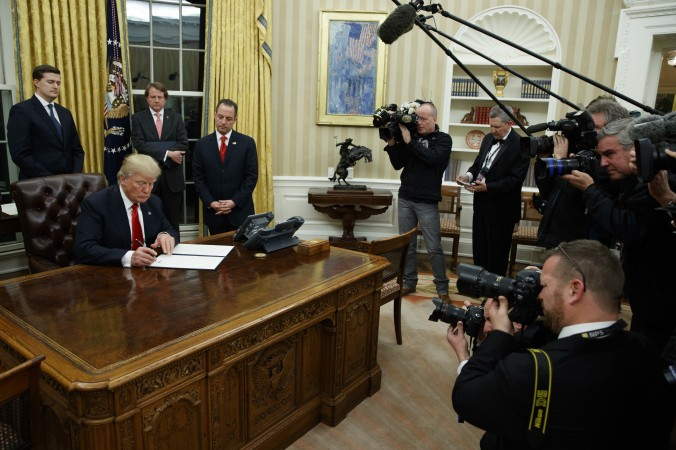 President Donald Trump signs his first executive order in the Oval Office of the White House in Washington on Jan. 20, 2017. (AP Photo/Evan Vucci)