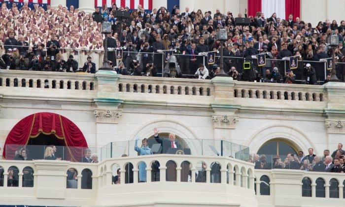 President Donald Trump with wife and First Lady, Melania Trump, wave after being sworn in during the 58th Presidential Inauguration at the U.S. Capitol in Washington, on Jan. 20, 2017. (Benjamin Chasteen/Epoch Times)