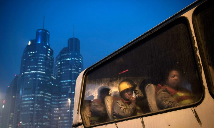 Chinese migrant workers wait in a bus as they leave after their shift at a construction site on Dec. 9, 2014 in Beijing, China. It is estimated that there are more than 40 million construction laborers in China, many of whom come from smaller centers to the country's larger cities to find work. (Kevin Frayer/Getty Images)