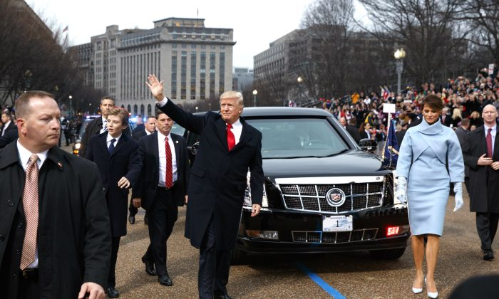 President Donald Trump waves to supporters as he walks the parade route with first lady Melania Trump and son Barron Trump after being sworn in at the 58th Presidential Inauguration in Washington, D.C on Jan. 20, 2017. (Evan Vucci - Pool/Getty Images)