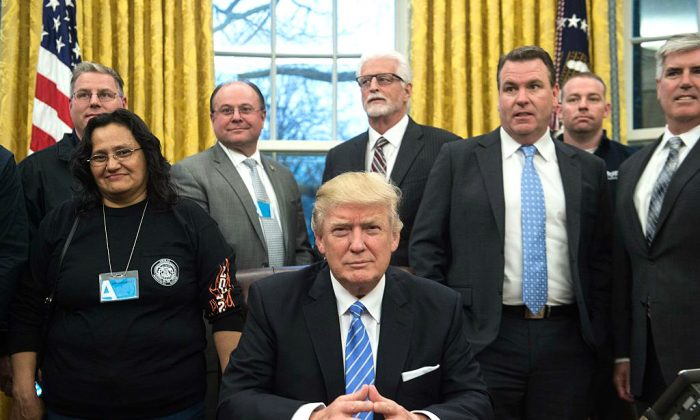 US President Donald Trump poses with labor leaders in the Oval Office at the White House in Washington, DC. on Jan. 23, 2017. (NICHOLAS KAMM/AFP/Getty Images)