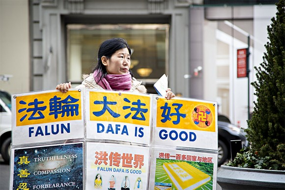 Wang Huijuan, in front of the Empire State Building in Manhattan, New York, on Jan. 12, 2017, holds a display to help Chinese tourists understand the facts about the persecution of Falun Gong in China. (Samira Bouaou/Epoch Times)