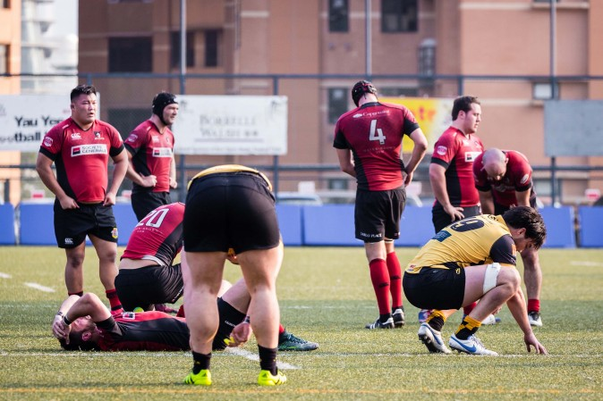Players gasp for air at the end of the HKRU Premiership game between Borrelli Walsh USRC Tigers (Yellow) and Societe Generale Valley at King's Park on Saturday Jan 21, 2017. (Dan Marchant)