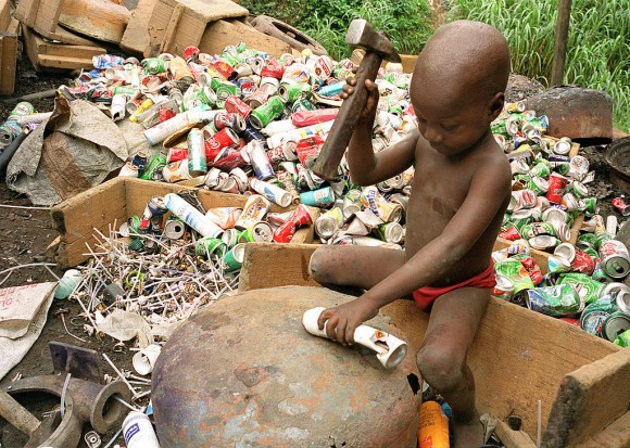 Alpha, 4, hits an aerosol can with a hammer for its aluminium to be reprocessed on Oct. 9, 1999, in Abidjan, Ivory Coast. Scrap aluminum is often used in Africa to make cooking pots, which release lead and other toxins into food, according to a study published in the February 2017 issue of the journal Science of the Total Environment. (Jean-Philippe Ksiazek/AFP/Getty Images)