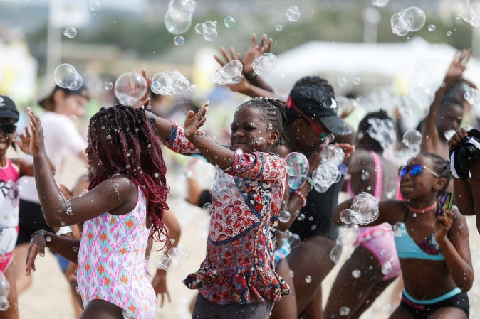 "Children play with soap bubble along the beach in Deauville, northwestern France, as part of the ""Forgotten by the Holidays"" campaign organized by the French NGO Secours Populaire for children whose families can not afford to go on holidays on on Aug. 23. (CHARLY TRIBALLEAU/AFP/Getty Images)"