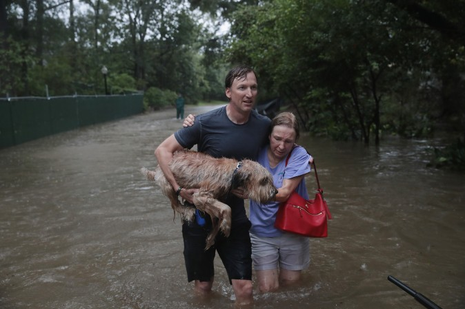 HOUSTON, TX - AUGUST 27: Andrew White (L) helps a neighbor down a street after rescuing her from her home in his boat in the upscale River Oaks neighborhood that was inundated with flooding from Hurricane Harvey in Houston on Aug. 27. (Scott Olson/Getty Images)