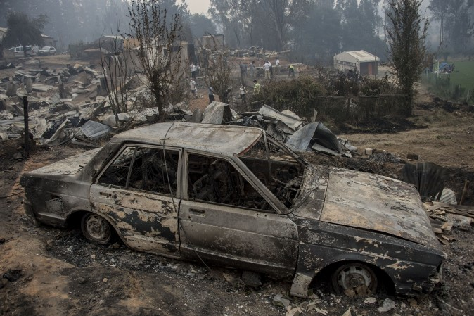 The town of Santa Olga, which was destroyed by a forest fire, 330 km south of Santiago, on Jan. 26. Six people -- among them four firefighters and two police -- have now been killed battling vast forest fires in central Chile, officials said Wednesday. Multiple blazes have ravaged 238,000 hectares (588,000 acres) and are growing, the National Forestry Corporation said in a statement. / AFP / MARTIN BERNETTI (MARTIN BERNETTI/AFP/Getty Images)