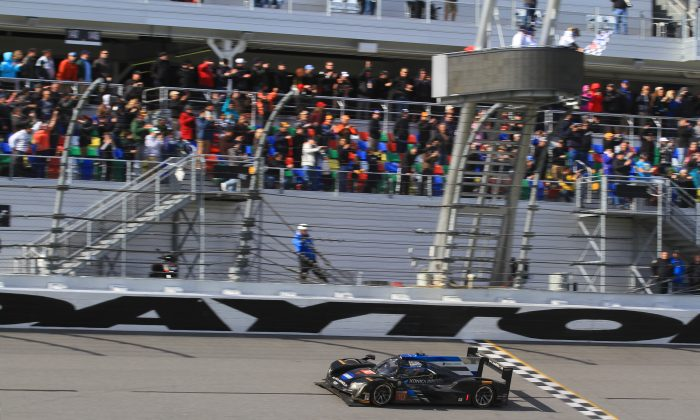 Ricky Taylor crosses the finish line in the #10 Wayne Taylor Racing Cadillac DPi after 24 hard hours of racing to win the 2017 IMSA WeatherTech Rolex 24 at Daytona, Jan. 29, 2017. (Chris Jasurek/Epoch Times)