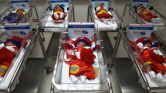 TOPSHOT - Newborn babies in Chinese-inspired costumes to mark the Year of the Rooster lay in cots at Paolo Memorial Hospital in Bangkok on January 27, 2017. / AFP / LILLIAN SUWANRUMPHA        (Photo credit should read LILLIAN SUWANRUMPHA/AFP/Getty Images)