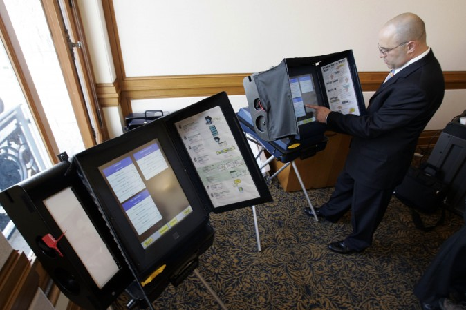 A sales executive with Sequoia Voting Systems, demonstrates how the machine works in San Francisco on Dec. 5, 2007. (AP Photo/Paul Sakuma)