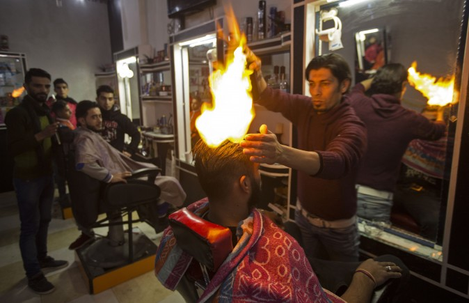 Ramadan Edwan, a Palestinian barber, uses fire in a hair-straightening technique with a client at his salon in the Rafah refugee camp, in the southern Gaza Strip on Feb. 1, 2017. (Mahmud Hams/AFP/Getty Images)
