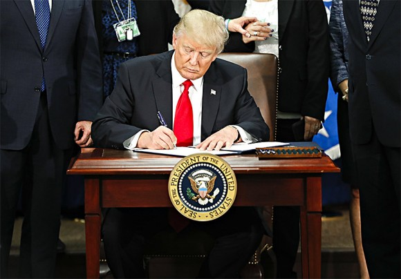 President Donald Trump at the Department of Homeland Security in Washington on Jan. 25 signs an executive order for increased border security and immigration enforcement. (AP Photo/Pablo Martinez Monsivais)