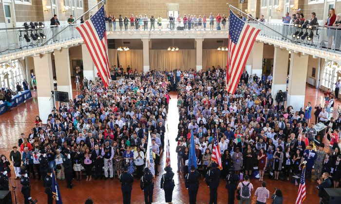 Immigrants stand for the national anthem during a naturalization ceremony in the Great Hall of Ellis Island in New York on Sept. 16, 2016. Nationwide, more than 730,000 people gained U.S. citizenship in 2015, which is just below the average number for the last 10 years. (John Moore/Getty Images)