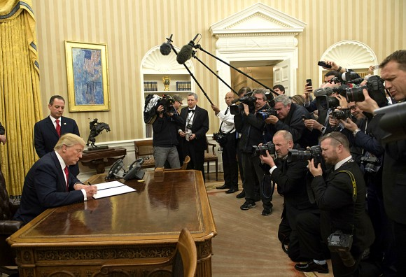 President Donald Trump signs his first executive order as president, ordering federal agencies to ease the burden of President Barack Obama's Affordable Care Act, at the White House on Jan. 20. (Kevin Dietsch - Pool/Getty Images)