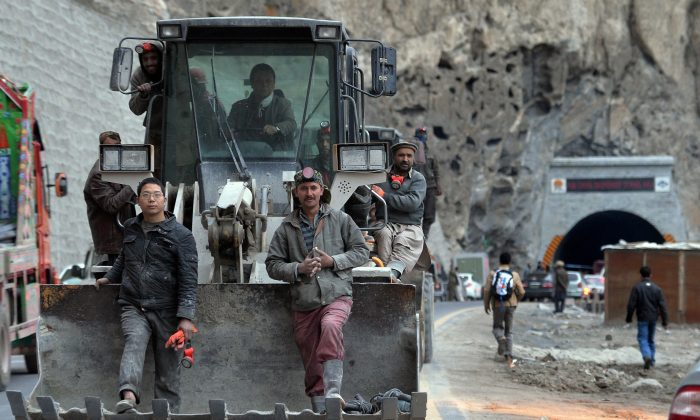 Pakistani and Chinese workers sit on an excavator as they leave the newly built tunnel in northern Pakistan's Gojal Valley, on Sept. 25, 2015. The project is part of China's ambitious One Belt, One Road initiative. (Aamir Qureshi/AFP/Getty Images)