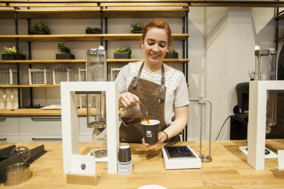 Extraction lab manager Meredith Enzbigilis pours freshly brewed coffee. The app-operated Steampunk frees the barista to chat with guests. (Channaly Philipp/Epoch Times)
