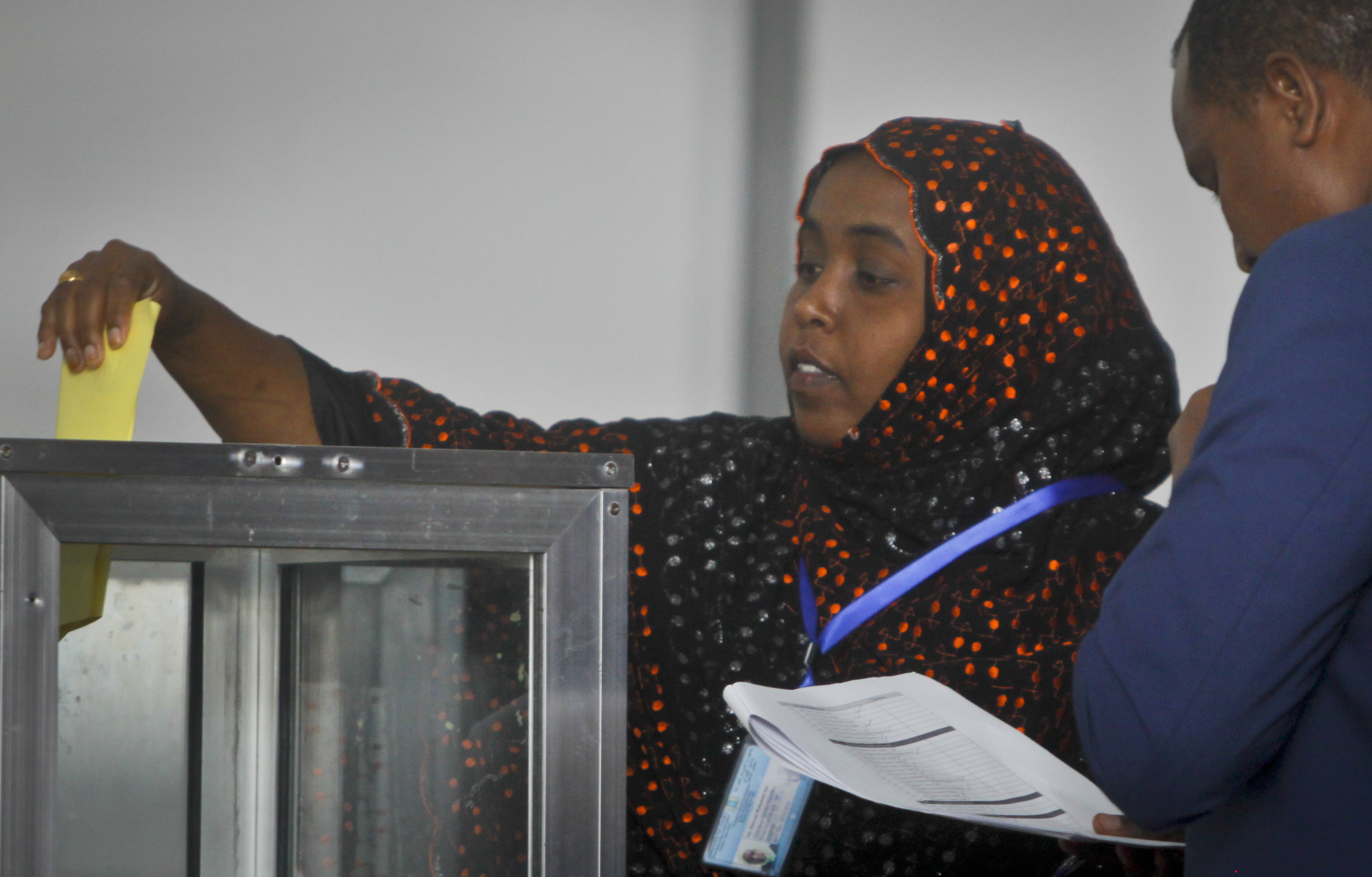 An unidentified Somali member of parliament casts her vote for the presidential election in Mogadishu, Somalia Wednesday, Feb. 8, 2017. Voting started Wednesday in Somalia's groundbreaking presidential election as members of the upper and lower houses of the legislature cast ballots in the first round with 21 candidates for president, amid a security lockdown that has closed the capital's international airport and cleared major streets. (AP Photo/Farah Abdi Warsameh)