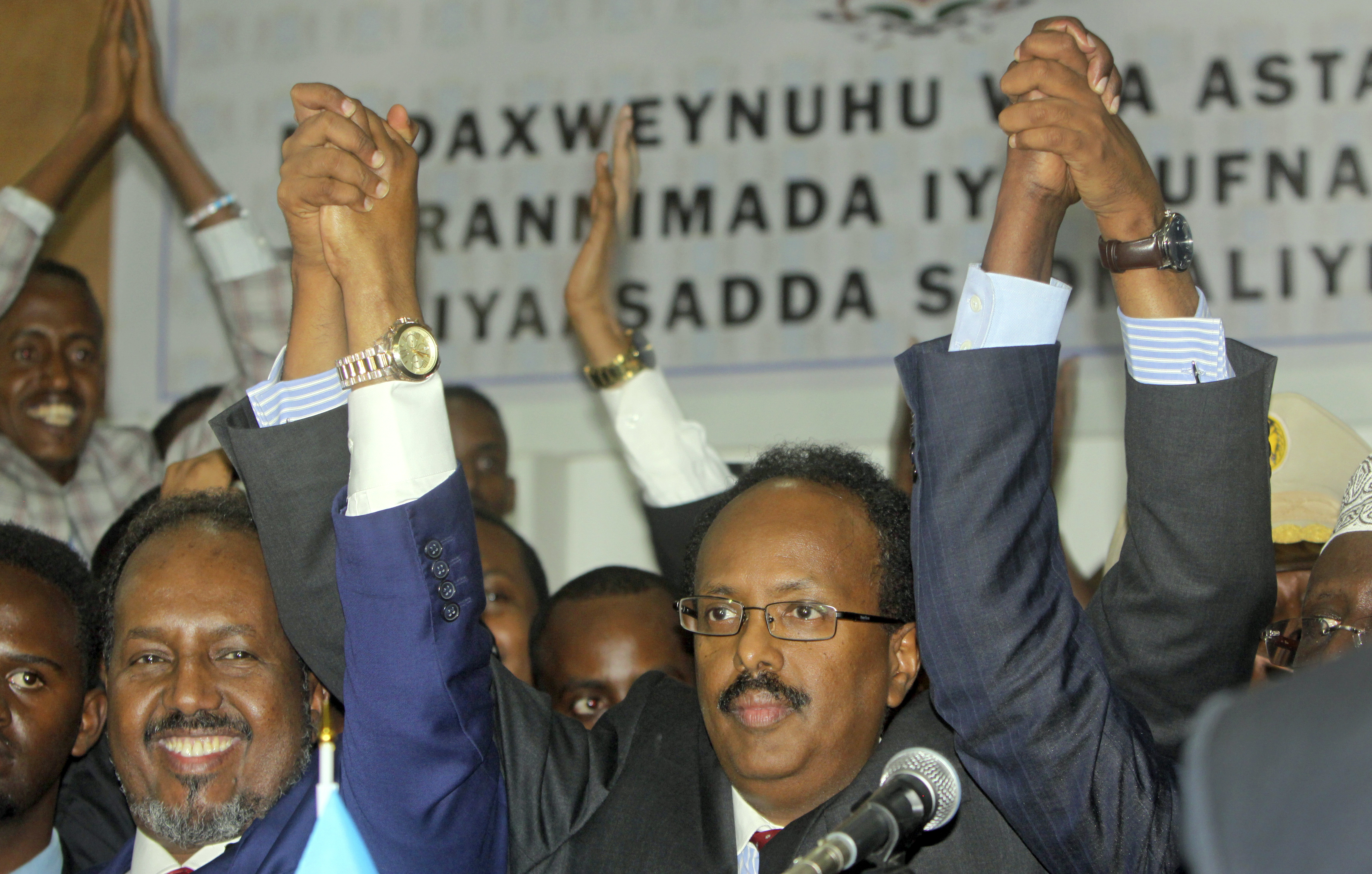 New Somali President Mohamed Abdullahi Farmajo (C) joins hands with incumbent President Hassan Sheikh Mohamud (L) as he celebrates winning the election and taking office in Mogadishu, Somalia on Feb. 8, 2017. (AP Photo/Farah Abdi Warsameh)
