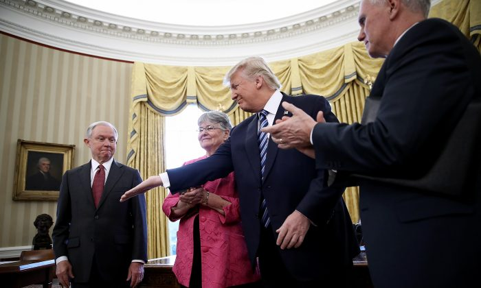 President Donald Trump (2nd R) reaches to shake the hand of  Jeff Sessions after Sessions was sworn in as the new U.S. Attorney General by U.S. Vice President Mike Pence (R) in the Oval Office of the White House in Washington on Feb. 9, 2017. Trump also signed three executive orders immediately after the swearing in ceremony. Also pictured is Sessions's wife, Mary (2nd L), holding the bible.  (Win McNamee/Getty Images)