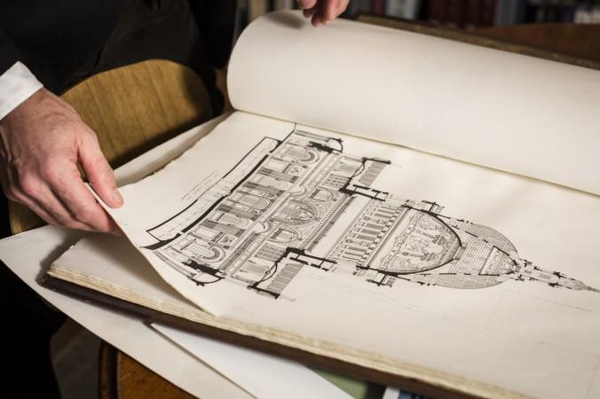 Richard Cameron shows one of the books in the library of Atelier & Co. architectural design firm in Williamsburg, Brooklyn, on Jan. 19, 2017. (Samira Bouaou/Epoch Times)