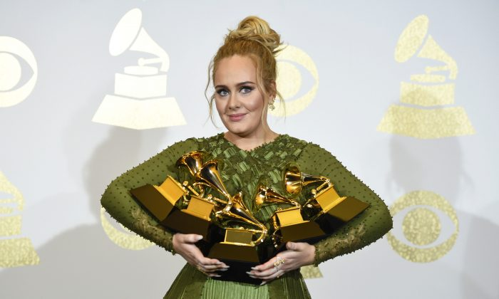 """Adele poses in the press room with the awards for album of the year for """"25"""", song of the year for """"Hello"""", record of the year for """"Hello"""", best pop solo performance for """"Hello"""", and best pop vocal album for """"25"""" at the 59th annual Grammy Awards at the Staples Center on Sunday, Feb. 12, 2017, in Los Angeles. (Photo by Chris Pizzello/Invision/AP)"""