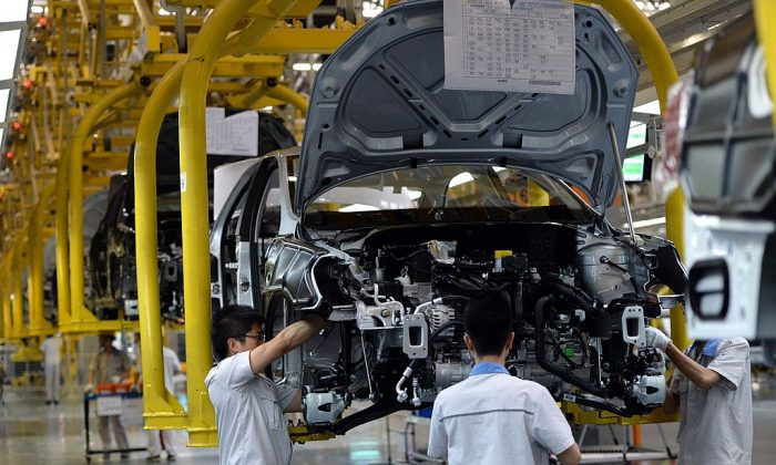 Chinese auto workers on the assembly line at the FAW-Volkswagen plant in Chengdu, southwest China's Sichuan province, during the visit of German Chancellor Angela Merkel on July 6, 2014. (GOH CHAI HIN/AFP/Getty Images)