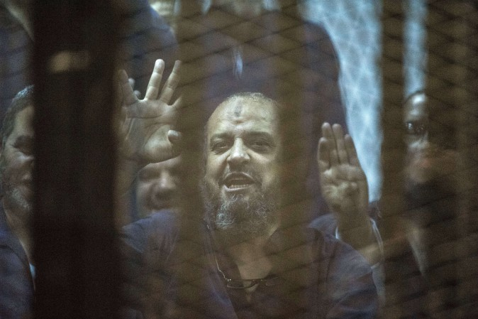 "Egyptian Muslim Brotherhood top figure, Mohamed el-Beltagy flashes the four finger symbol known as ""Rabaa"" from behind the defendant's cage as the judge reads out the verdict sentencing him and more than 100 other defendants  at the police academy in Cairo on May 16, 2015. (KHALED DESOUKI/AFP/Getty Images)"