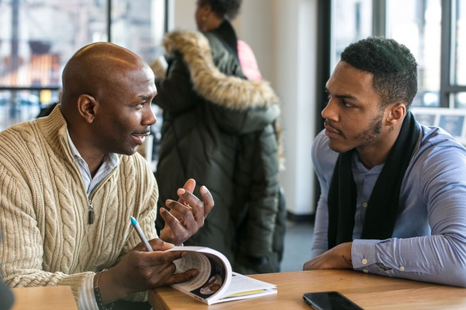 Author and motivational speaker Dwayne Bryant, talks with former gang member Deandre Robertson at a new Chipotle in Englewood, Chicago, on Feb. 1, 2017. (Benjamin Chasteen/Epoch Times)