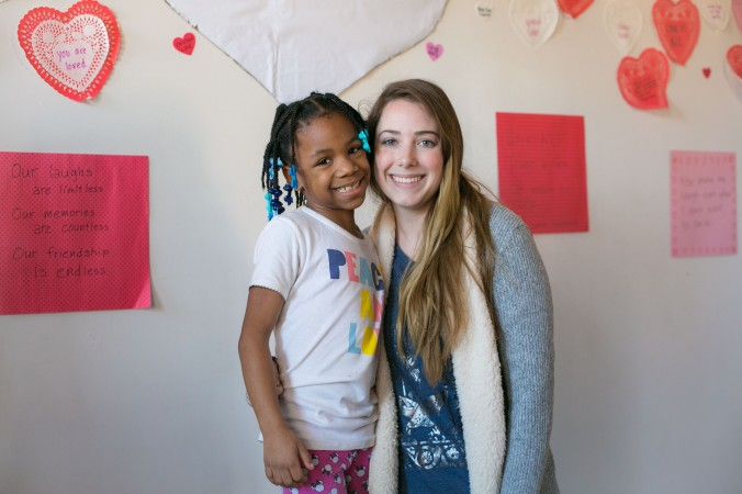 Erin Vogel, co-executive director of I Grow Chicago with a little girl who lives next door at the I Grow Chicago Peace House in Englewood, Chicago, on Feb. 2, 2017. (Benjamin Chasteen/Epoch Times)