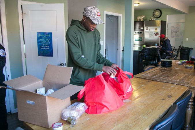 Karl Mables fills bags with food which was given to them by the local Whole Foods Market, to give out to people in the community who needs them at the I Grow Chicago Peace House in Englewood, Chicago, on Feb. 3, 2017. (Benjamin Chasteen/Epoch Times)