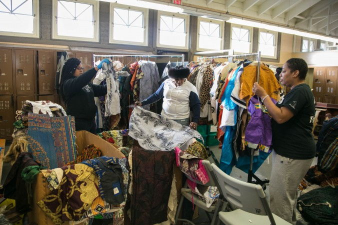 Woman from the Resident Association of Greater Englewood (R.A.G.E.) organization, prepare traditional African American clothes to sell at a community fund raiser at Hamilton Park in Englewood, Chicago, on Feb. 3, 2017. (Benjamin Chasteen/Epoch Times)