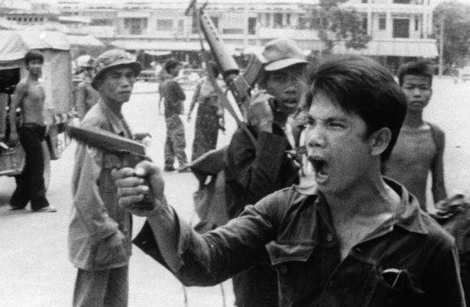 A Khmer Rouge soldier waves his pistol and orders store owners to abandon their shops in Phnom Penh, Cambodia, on April 17, 1975 as the capital fell to the communist forces. (AP Photo/Christoph Froehder)