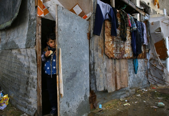 A Palestinian boy stands at the entrance of his family's impoverished house near the ruins of a building in Beit Hanun in the northern Gaza Strip on Feb. 15, 2017. (MOHAMMED ABED/AFP/Getty Images)