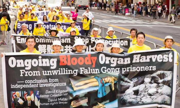 Falun Gong practitioners hold a banner in reference to the organ harvesting of practitioners which is still happening today inside China. (Edward Dye/Epoch Times)