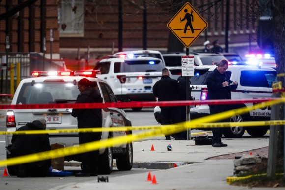 Crime scene investigators collect evidence from a scene where Abdul Razak Ali Artan rammed his Honda Civic into a crowd of people and then took out a knife and slashed 13 people on the campus of Ohio State University in Columbus on Nov. 28, 2016.  (AP Photo/John Minchillo)