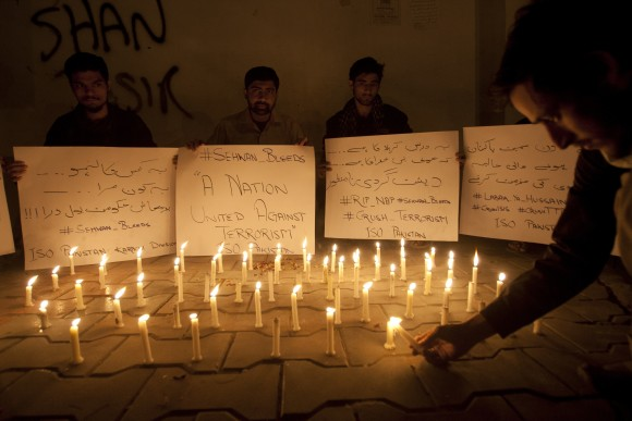 Pakistani students light candles to condemn the recent attack on a shrine in interior Sind province, in Karachi, Pakistan, on Feb. 16, 2017. (AP Photo/Shakil Adil)