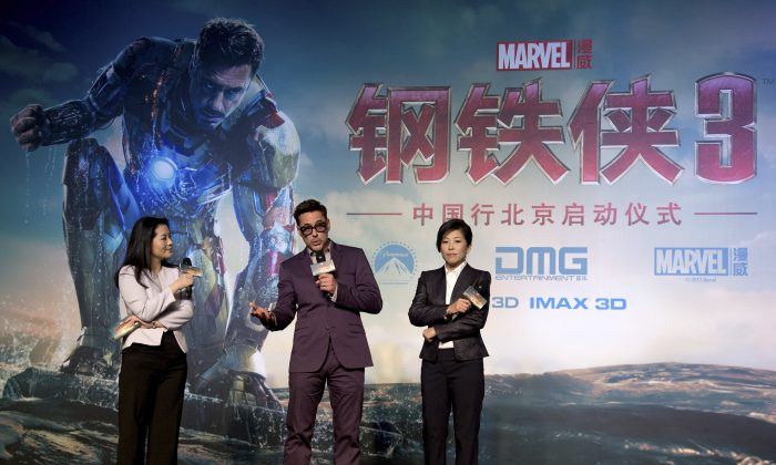 "Robert Downey Jr,  on stage with DMG president Wu Bing (R) during the the world premiere event of ""Iron Man 3,"" in Beijing on April 6, 2013. (AP Photo/Andy Wong)"