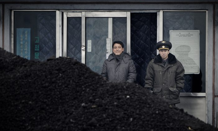 A North Korean military officer (R) and a North Korea man (L) standing behind a pile of coal along the banks of the Yalu River in the northeast of the North Korean border town of Siniuju, on December 14, 2012. On Feb. 18, the Chinese Commerce Ministry announced a suspension of all North Korean coal imports. (Wang Zhao/AFP/Getty Images)