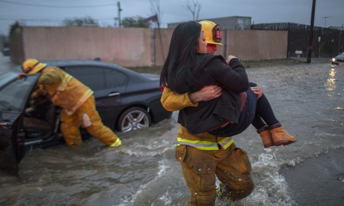 A firefighter carries a woman from her car after it was caught in street flooding as a powerful storm moved across Southern California in Sun Valley, Calif. on Feb. 17. (Photo by David McNew/Getty Images)