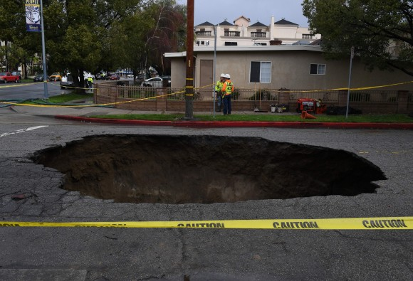 A 20-foot sinkhole that swallowed two vehicles in North Laurel Canyon Blvd, in Los Angeles, is cordoned-off on Feb. 18, after a powerful storm hit Southern California. (Photo credit should read MARK RALSTON/AFP/Getty Images)