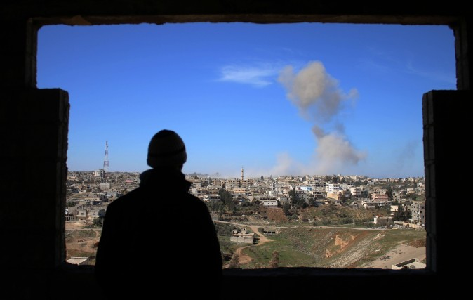 A man looks at smoke billowing after a reported car bomb explosion during clashes between rebel fighters and regime forces to take control of an area in the southern city of Daraa, Syria, on Feb. 20, 2017. (Mohamad Abazeed/AFP/Getty Images)