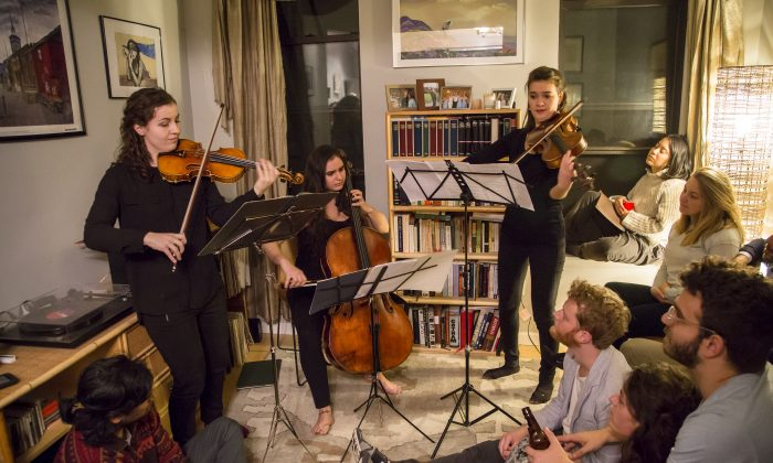 (L-R) Rannveig Marta Sarc on violin, Clara Abel on cello, and Chloé Thominet on viola perform at a Groupmuse house concert in Harlem, New York, on Feb. 17, 2017. (Samira Bouaou/Epoch Times)