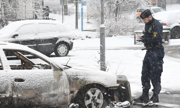 A police man investigate a burned out car in the suburb Rinkeby outside Stockholm, Tuesday Feb. 21, 2017.  Swedish police on Tuesday were investigating a riot that broke out Monday night in a predominantly immigrant suburb in Stockholm after officers arrested a suspect on drug charges. The clashes started late Monday when a police car arrested a suspect and people started throwing stones at them. (Fredrik Sandberg / TT via AP)