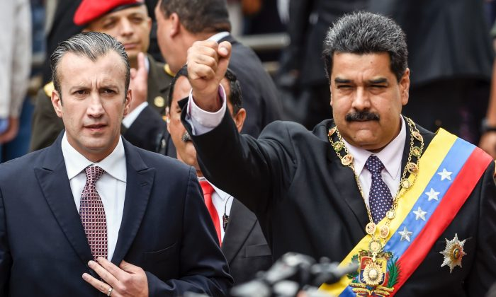 Venezuelan President Nicolas Maduro (R) and Vicepresident Tareck El Aissami greet supporters before the ceremony where Maduro gave a speech reviewing his year in office at the Supreme Court of Justice in Caracas on Jan. 15, 2017. 
