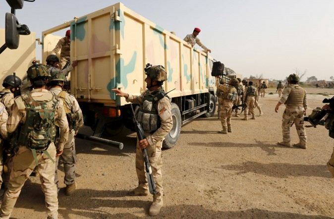 Iraqi security forces climb into trucks travelling to Mosul to fight against ISIS terrorists at an Iraqi army base in Camp Taji, Baghdad, on Feb. 21, 2016. (REUTERS/Ahmed Saad)