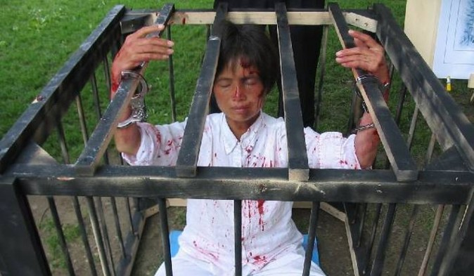 A Falun Gong practitioner protests by posing in a cage (Minghui)
