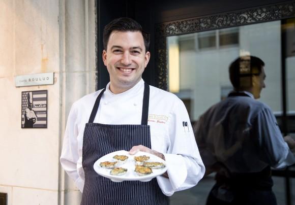 Aaron Bludorn, executive chef of Café Boulud, holds a plate of Oysters Rockefeller. (Samira Bouaou/Epoch Times)