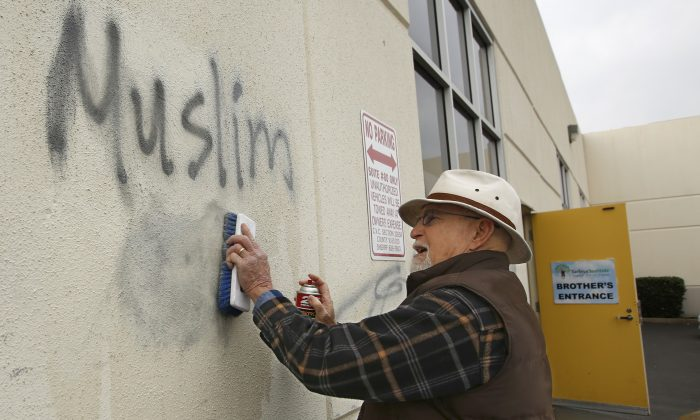 Tom Garing cleans up racist graffiti painted on the side of a mosque in what officials are calling an apparent hate crime in Roseville, Calif. on Feb. 1, 2017. (AP Photo/Rich Pedroncelli)